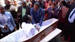 A man touching a man in coffin