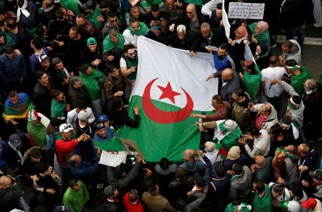 Demonstrators hold flags and banners as they return to the streets to press demands for wholesale democratic change well beyond former president Abdelaziz Bouteflika's resignation in Algiers, Algeria.
