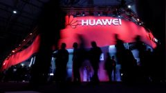 Visitors walk past Huawei's booth during Mobile World Congress in Barcelona.