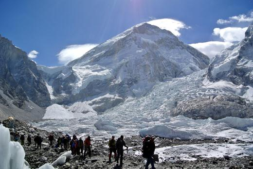Climbers walk towards their helicopter (not seen) after their Mount Everest expeditions were cancelled