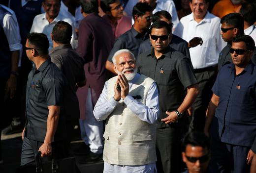 India's Prime Minister Narendra Modi greets his supporters after casting his vote outside a polling station.