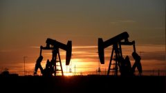 Pump jacks operate at sunset in an oilfield in Midland