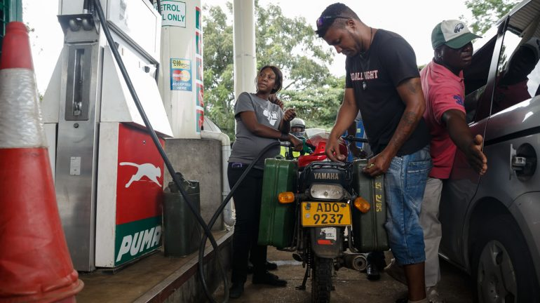 A petrol attendant serves a motorcyclist with two jerry cans attached to his motorbike at a fuel station