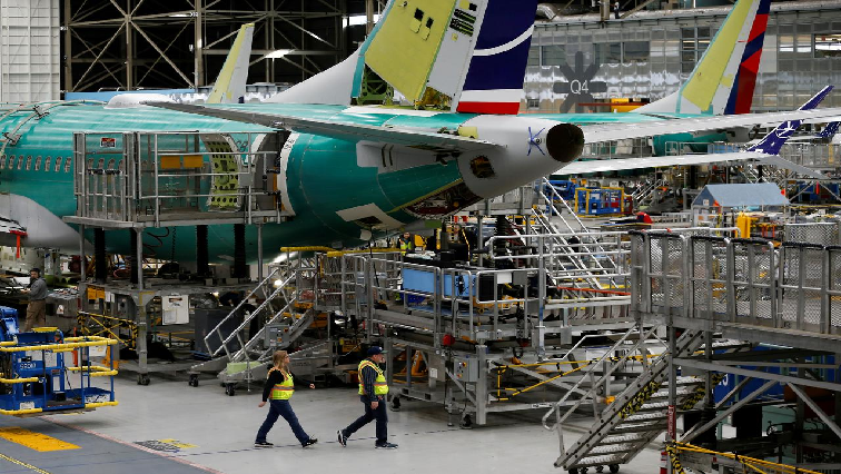 Employees walk by the end of a 737 Max aircraft at the Boeing factory in Renton.