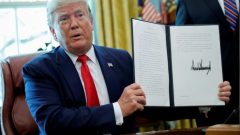 US President Donald Trump displays an executive order imposing fresh sanctions on Iran in the Oval Office of the White House in Washington, US