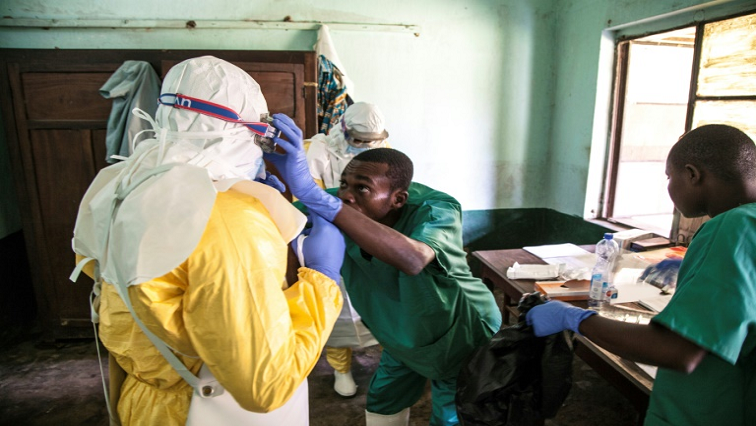 Health workers don protective equipment