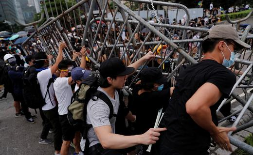 Demonstrators attempt to move metal barricades during a protest against a proposed extradition bill in Hong Kong.