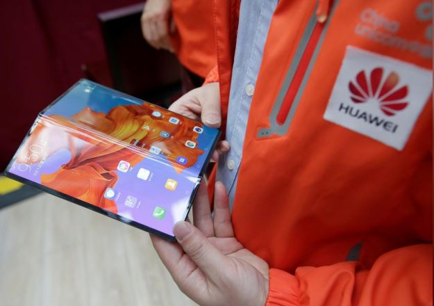 A staff member shows the new Huawei Mate X smartphone with 5G network provided by China Unicom and Huawei at the media center for the Chinese People's Political Consultative Conference (CPPCC) and the National People's Congress (NPC) in Beijing.