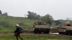 An Israeli soldier walks past armoured Israeli military vehicles in the Israeli-occupied Golan Heights.