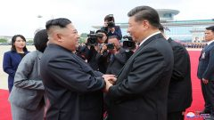 Kim Jong Un and Xi Jinping greeting each other