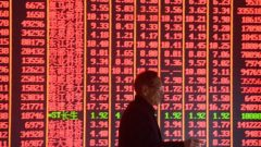 A man walks past a share index board