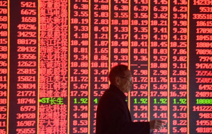 A man is seen in front of an electronic board showing stock information on the first day of trading in the Year of the Pig, following the Chinese Lunar New Year holiday, at a brokerage house in Hangzhou.