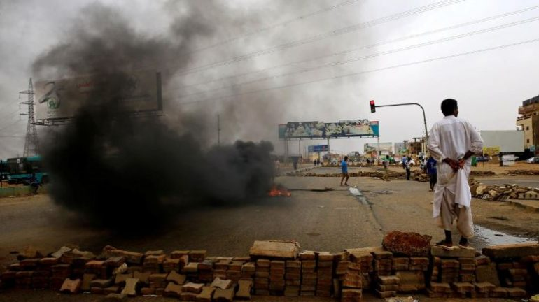 A Sudanese protester stands near a barricade on a street, demanding that the country's Transitional Military Council handover power to civilians, in Khartoum, Sudan.