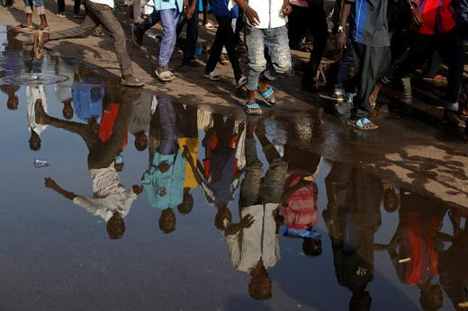 Protesters are reflected on a puddle as they march near the Defence Ministry in Khartoum, Sudan