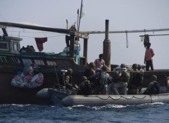 The United States Navy search and seizure team from The Arleigh Burke-class guided-missile destroyer USS McFaul's (DDG 74) speak to fishermen aboard a Bahraini dhow during routine maritime security operations in Arabian Sea.