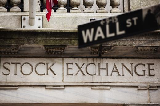A street sign for Wall Street hangs in front of the New York Stock Exchange.