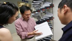 "Scientist He Jiankui shows ""The Human Genome"", a book he edited, at his company Direct Genomics in Shenzhen,"