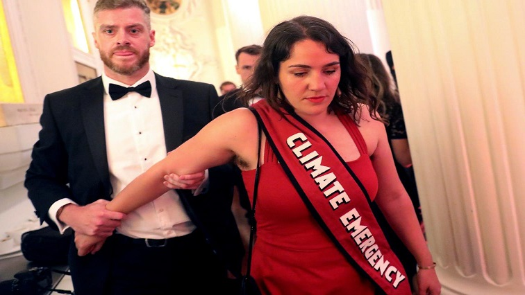 A climate change protester is escorted out after interrupting a speech during the annual Mansion House dinner in London