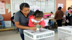 A voter carries a child as she casts her ballot at a polling station