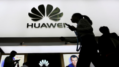 A person walking and holding a Huawei handset