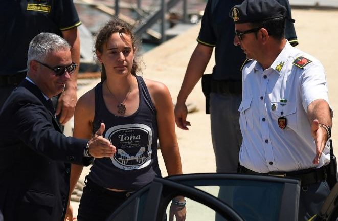 Carola Rackete, the 31-year-old Sea-Watch 3 captain, disembarks from a Finance police boat and is escorted to a car, in Porto Empedocle.