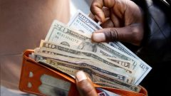 A man displays US dollar notes after withdrawing cash from a bank in Harare, Zimbabwe