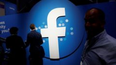 Attendees walk past a Facebook logo in San Jose, California.