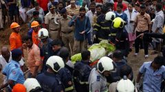 Rescue workers carry the body of a victim after a wall collapsed at a slum in Mumbai, India.