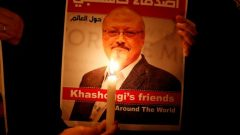 A demonstrator holds a poster with a picture of Saudi journalist Jamal Khashoggi outside the Saudi Arabia consulate.