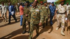 General Jamal Omar, center, a member of Sudan's Transitional Military Council (TMC), arrives in the capital Khartoum's twin city of Omdurman.