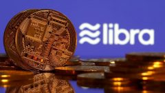 Representations of virtual currency are displayed in front of the Libra logo in this illustration picture.