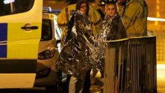 Two women wrapped in thermal blankets stand near the Manchester Arena, where U.S. singer Ariana Grande had been performing, in Manchester.