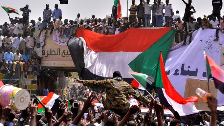 A military officer is carried by the crowd as demonstrators chant slogans and carry their national flags, after Sudan's Defense Minister said that President Omar al-Bashir had been detained 'in a safe place'.