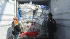 Indonesian officers check a container full with illegal imported plastics waste in Batam on July 29, 2019. Indonesia has returned seven shipping containers of illegally imported waste to France and Hong Kong, an official.