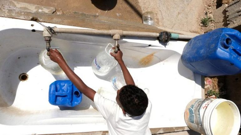 A Libyan boy displaced from the town of Tawergha fills containers with water at a displaced camp in Benghazi, Libya.