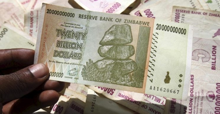 A man poses with Zimbabwean bank note at a bank in central Harare