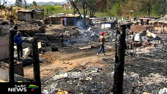 A man walking pass a burnt home