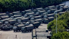 Service men walk past military vehicles in the parking area of the Shenzhen Bay Sports Center in Shenzhen across the bay from Hong Kong.