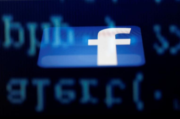 A Facebook logo on an Ipad is reflected among source code on the LCD screen of a computer, in this photo illustration taken in Sarajevo
