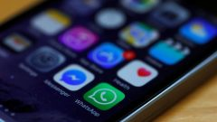 WhatsApp and Facebook messenger icons are seen on an iPhone in Manchester.