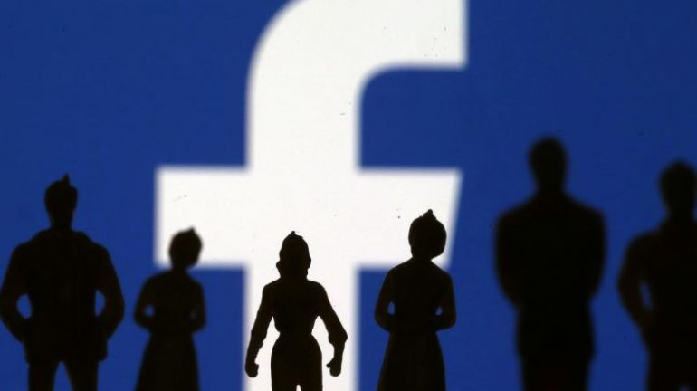 Small toy figures are seen in front of Facebook logo in this illustration picture.