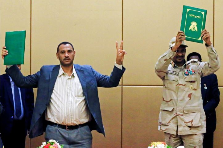Deputy Head of Sudanese Transitional Military Council, Mohamed Hamdan Dagalo and Sudan's opposition alliance coalition's leader Ahmad al-Rabiah hold up signed copies of the constitutional declaration during a signing ceremony in Khartoum.