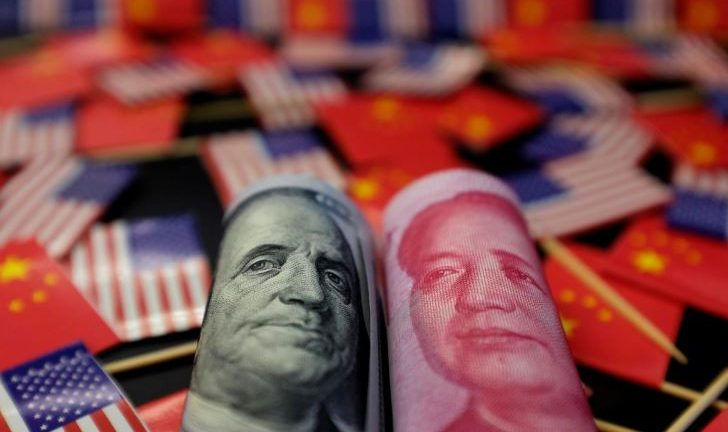 A U.S. dollar banknote featuring American founding father Benjamin Franklin and a China's yuan banknote featuring late Chinese chairman Mao Zedong are seen among U.S. and Chinese flags in this illustration.