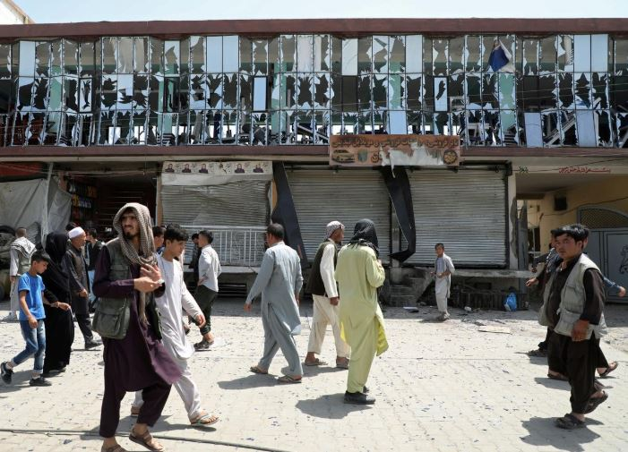 People walk in front of a building with broken windows at the site of a car bomb blast in Kabul, Afghanistan.