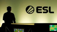 A gamer is silhouetted against an illuminated wall with the logo of the Electronic Sports League ESL