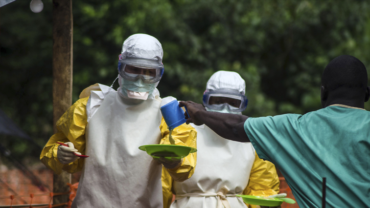 Health workers dressed in protective suits