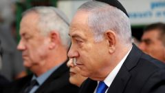 Israeli Prime Minister Benjamin Netanyahu looks on as he sits next to Benny Gantz, leader of the Blue and White party, during a memorial ceremony for late Israeli President Shimon Peres, at Mount Herzl in Jerusalem.