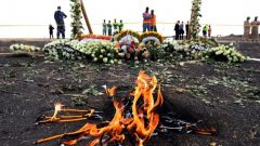 Candle flames burn during a commemoration ceremony for the victims at the scene of the Ethiopian Airlines Flight ET 302 plane crash, near the town Bishoftu, near Addis Ababa.