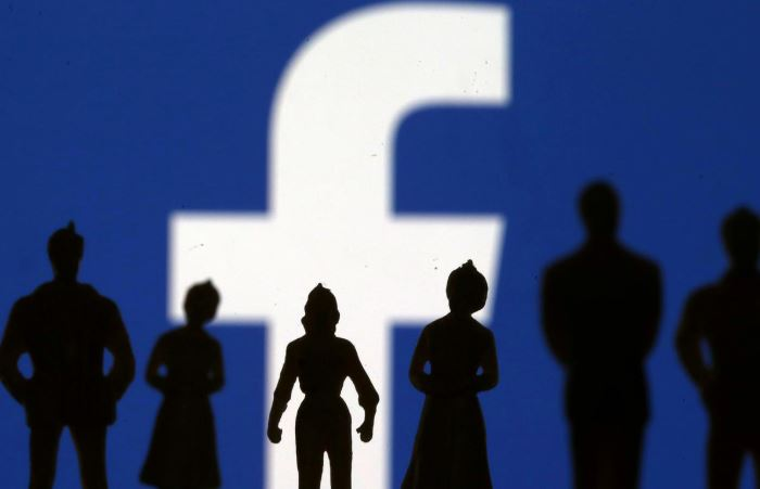 Small toy figures are seen in front of Facebook logo in this illustration.
