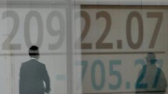 Men are reflected on an electronic board showing the Nikkei stock index outside a brokerage in Tokyo.